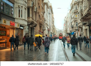 Istanbul, Turkey - April 14, 2019: people in the street at the europian part of Istanbul, Istiqlal Boulevard. Red nostalgic tram far avay. Rainy day.
