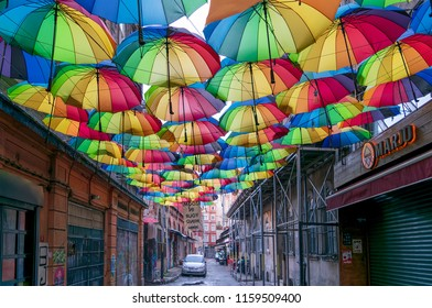 Istanbul, Turkey - April 18, 2017: Hoca Tahsin Street at Karakoy district decorated with colorful umbrellas with few people walking before sunset