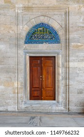 Istanbul, Turkey - April 21, 2017: Wooden engraved door on stone wall and tiled marble floor, Sulaymaniye Mosque, Istanbul, Turkey