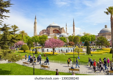 Istanbul, Turkey - April 22, 2017: Low aerial view of Sultanahmet district of Istanbul, Turkey. Walking people, green grass field and fountain near famous landmark Hagia Sophia.