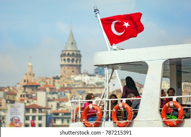 Istanbul, Turkey - April 23, 2017: Tourists travel by ferry with red turkish flag across Golden Horn inlet on background of famous Galata Tower in Istanbul, Turkey.