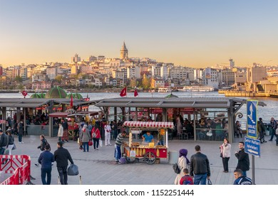 Istanbul, Turkey - April 25, 2017: Eminonu Piazza before sunset with local citizens buying food from carts and floating seafood restaurants with city view of Istanbul overlooking Galata Tower