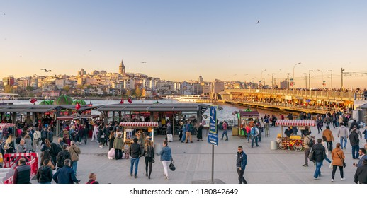 Istanbul, Turkey - April 25, 2017: Eminonu Piazza before sunset with local citizens buying food from carts and floating seafood restaurants with city view including Galata Tower and Galata Bridge