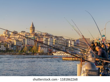 Istanbul, Turkey - April 25, 2017: Local citizens fishing at golden horn on Galata Bridge before sunset with Galata Tower in the background, Eminonu district, Istanbul, Turkey