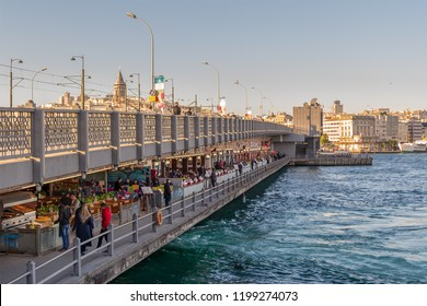 Istanbul, Turkey - April 25, 2017: Galata Bridge with traditional fish restaurants in the passage under the bridge overlooking Galata Tower in the far distance before sunset