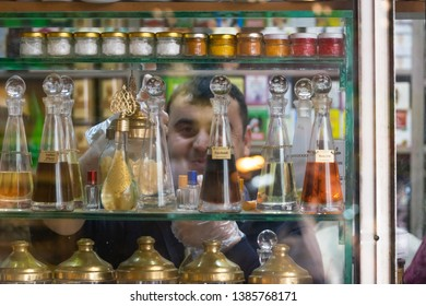 Istanbul, Turkey - April 27, 2019: Man seller behind the glass vitrine smiling to the camera. Store with essential asian oils and herbs.