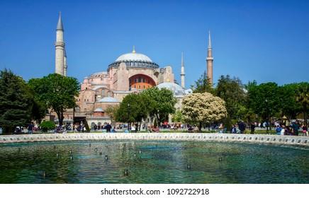 ISTANBUL, TURKEY - APRIL 30, 2018: Tourists walking in the Sultanahmet Park near Hagia Sophia (Ayasofya) museum in Istanbul, Turkey.