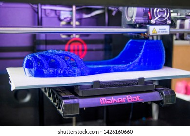 ISTANBUL, TURKEY, AUGUST 15, 2014: Close up shot of Makerbot branded 3D printer, printing a blue sandal type shoe.
