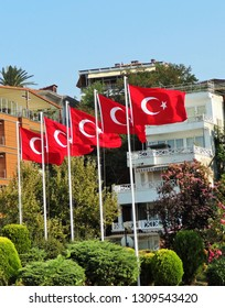 Istanbul Turkey - August 5 2012: Close up of Five Turkish Flags on poles near buildings and green trees and bushes
