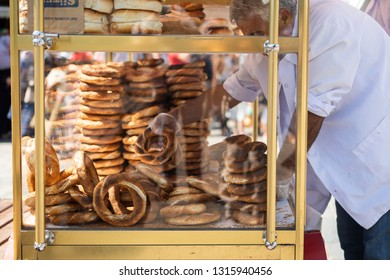 ISTANBUL, TURKEY, AUGUST 9, 2018: unidentified man sells Simit in the street of Istanbul. Simit is a popular Turkish street food made of a twisted circles of dough with sesame