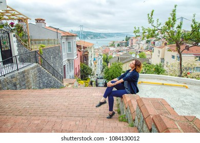 ISTANBUL, TURKEY: Beautiful girl sitting on a stair in Kuzguncuk district with view of Bosphorus and Bosphorus Bridge on background, on May 5, 2018