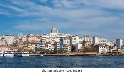 Istanbul, Turkey - Circa December 2017 - A panoramic shot of Galata Tower with surrounding buildings on a clear day taken from the Golden Horn waterway