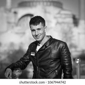 Istanbul, Turkey - Circa December 2017 - A black and white portrait shot of an unidentified Turkish guy wearing a black leather jacket on a sunny winter day