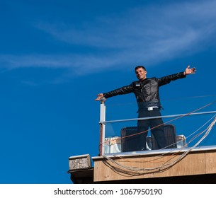 Istanbul, Turkey - Circa December 2017 - A portrait shot of an unidentified Turkish guy wearing a black leather jacket standing on a hotel rooftop on a sunny winter day with a blue sky background