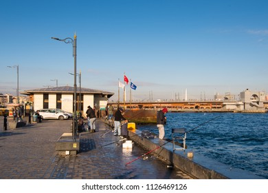 Istanbul, Turkey - Circa December 2017 - A shot of unidentified local Turkish men fishing at the Golden Horn waterway which is considered as a favoutire pastime activity for them