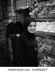 Istanbul, Turkey - Circa December 2017 - A portrait shot of an unidentified young and beautiful Turkish woman smiling who sells spices and sweets at the Spice Bazaar in Istanbul