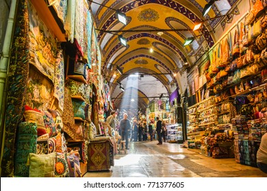 Istanbul, Turkey - December 2, 2017: People shopping in the Grand Bazar, handmade pillows, bags and carpets are on the wall for sale. The sunlight comes to inside from roof window.