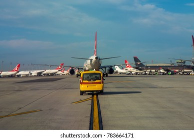 ISTANBUL / TURKEY - DECEMBER 2017 A Marshalling car is guiding a plane to its parking position across the busy IST aprons behind a Turkish Airlines Airbus A321.