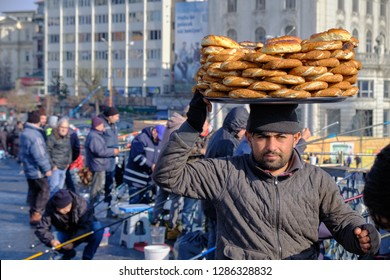 Istanbul, Turkey - December 2018 : Man selling simit (round traditional turkish bread) to the fisherman on Galata bridge.  Portrait shot with seller carrying simit on his head