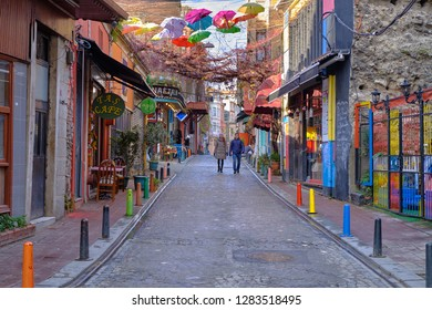 Istanbul, Turkey- December 2018: Pedestrians walking down a street in colorful Balat area of Istanbul on a cold December day.