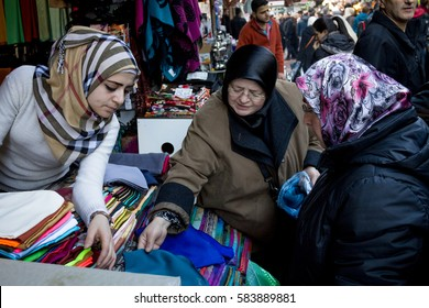 ISTANBUL, TURKEY - DECEMBER 28, 2015: Group of women wearing islamic headscarf negotiating clothe at a fabric merchant on a bazzar on the European side of the city