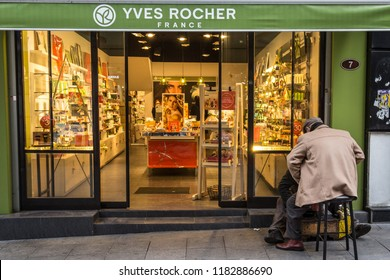 ISTANBUL, TURKEY - DECEMBER 29, 2015: Shoeshiner polishing shoes in front of the local Yves Rocher store with its sign. Yves Rocher is a French cosmetics and beauty brand