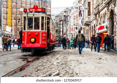 ISTANBUL, TURKEY - December 31, 2015: Snowy day in Taksim, Beyoglu. Nostalgic tram in Istiklal Street. Taksim Istiklal Street is a popular destination in Istanbul, Turkey.