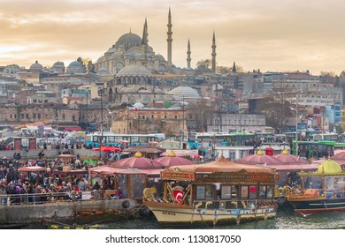 ISTANBUL, TURKEY -FEB 1, 2013: Crowded people in Eminonu district with  the Suleymaniye Camii mosque at the skyline (view from Galata bridge). This mosque is one of the best-known sights of Istanbul.