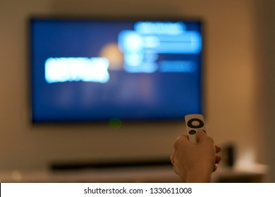 ISTANBUL, TURKEY - FEB28, 2019: A hand holding a remote for an Apple TV with the NETFLIX on a TV in the background
