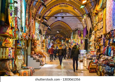 ISTANBUL, TURKEY - FEBRUARY 1, 2019: People shopping in the Grand Bazar, handmade pillows, bags and carpets are on the wall for sale.