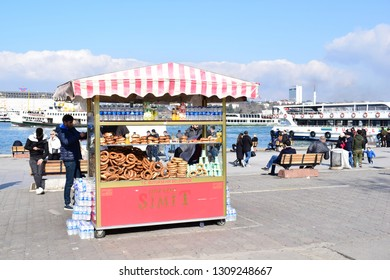 ISTANBUL, TURKEY - FEBRUARY 10, 2019: Simit seller in Kadıköy, a major district on the Asian side of Istanbul. Simit is a traditional circular bread, encrusted with sesame seeds.