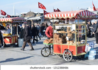 ISTANBUL, TURKEY - FEBRUARY 11, 2019: Simit seller in Eminönü, the historical center of Istanbul. Simit is a traditional circular bread, encrusted with sesame seeds.