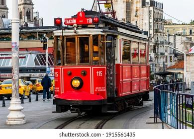 ISTANBUL, TURKEY - February 11, 2021: Nostalgic red tram in Taksim Square. Istiklal Street is a popular touristic destination in Istanbul, Turkey.