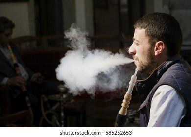 Istanbul, Turkey - February 19, 2017: A Turkish Man is blowing smoke. He is actually smoking hookah.
