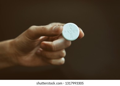 ISTANBUL, TURKEY, FEBRUARY 19, 2019: Female hand holding Aspirin tablets, known as acetylsalicylic acid (ASA), is a medication used to treat pain, fever, or inflammation.