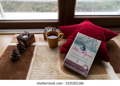Istanbul/ Turkey -February 23,2019; The cup of tea or coffee with Nazan Bekiroglu Nar agaci book and candle on the wooden table near the window on the rainy weather.