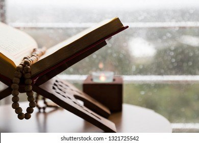 Istanbul / Turkey -February 23,2019; Quran and rosary beads on the wooden background with candle for Islamic concept. Holy book Koran for Muslims holiday, Ramadan,blessed Friday message