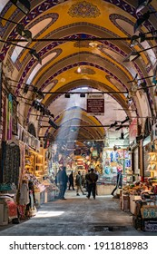 Istanbul, Turkey - February 5, 2021: People shopping in the Grand Bazar, handmade lamps, bags and carpets  for sale. The sunlight comes to inside from roof window.