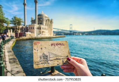 ISTANBUL, TURKEY: Female hand with a postcard depicting the Ortakoy mosque and the Ortakoy mosque and the Bosporus bridge in the background on October 5, 2017