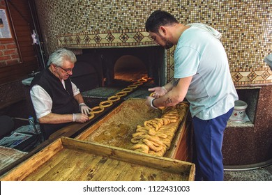 ISTANBUL, TURKEY: Historical bakery in Karakoy. Bakers in the process of preparing turkish bagels with sesame - simit, for baking in the oven on April 21, 2018
