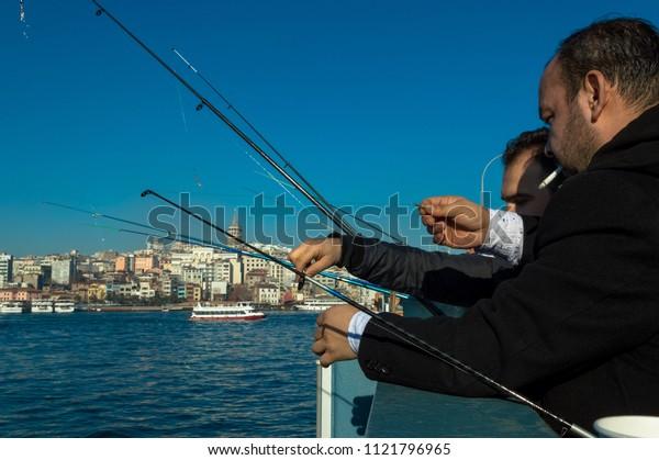 Istanbul, Turkey - January 06, 2018: Local fishermen fishing on Galata Bridge to relax and enjoy their hobby in Istanbul, Turkey.