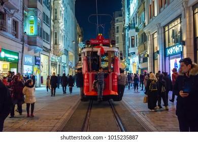 ISTANBUL, TURKEY - JANUARY 1, 2018: Nostalgic Red Tram in Taksim Istiklal Street at evening. Taksim Istiklal Street is a popular destination in Istanbul. Beyoglu, Taksim, Istanbul. Turkey.
