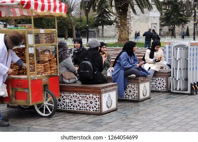 ISTANBUL, TURKEY - JANUARY 13, 2018: Unidentified muslim tourists eat bagels in Sultanahmet square