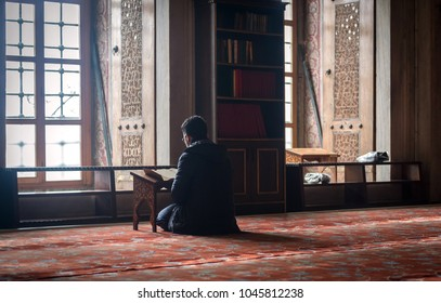 ISTANBUL, TURKEY - JANUARY 14: Muslim who reads the Qur'an, Sultanahmet Mosque on January 14, 2018 in Istanbul, Turkey. Blue Mosque, built in the 17th century by the architect Mehmet Aga.