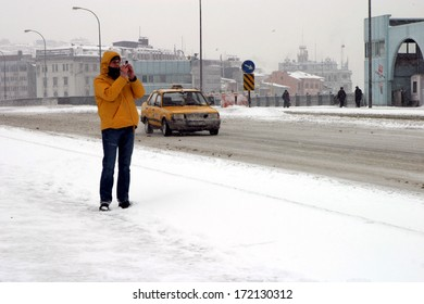 ISTANBUL, TURKEY - JANUARY 23: Tourist take a photo a snowy day at Galata Bridge in Karakoy Coastline on January 23, 2007 in Istanbul, Turkey.