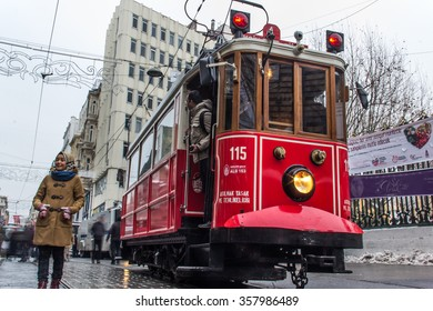 ISTANBUL, TURKEY - JANUARY 3, 2016: Retro tram moves along a busy Istiklal street in Istanbul. Red train to Istiklal Street after rainy and snow. There are reflections