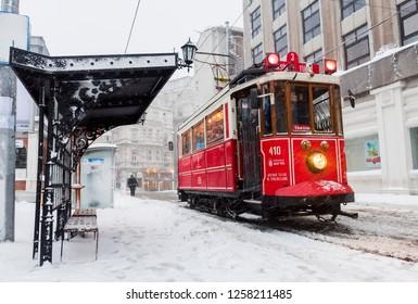 ISTANBUL, TURKEY - JANUARY 7, 2017: Snowy day in Taksim, Beyoglu. Nostalgic tram in Istiklal Street. Taksim Istiklal Street is a popular destination in Istanbul, Turkey.