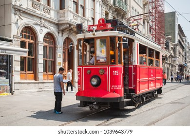 Istanbul, Turkey - July 1, 2016: Traditional red tram on Istiklal street in Istanbul, popular public and tourist transport, ordinary people walk on street