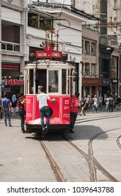 Istanbul, Turkey - July 1, 2016: Classic red tram goes on Taksim square in Istanbul, boys ride for free on the bumper