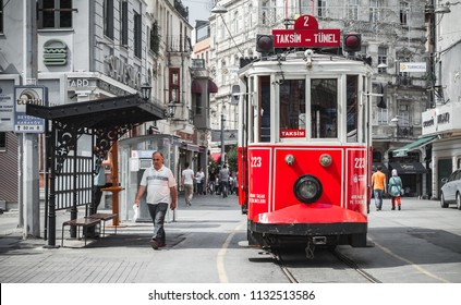 Istanbul, Turkey - July 1, 2016: Red tram goes on Istiklal street in Istanbul, ordinary people walk the street